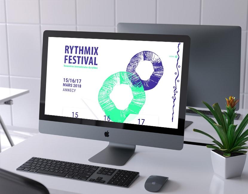 Photographie d'un ordinateur sur un bureau. Dans l'écran, on voit l'accueil du site du festival fictif Rythmix. Il reprend des formes vectorisées vertes fluos et bleues foncées, avec le titre du festival et les dates.