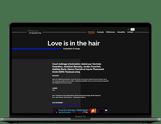Photographie d'un ordinateur. Dans l'écran, on voit, sur fond noir, le détail d'un projet sur lequel Thérence à Travaillé. Il y a le titre du projet, et plusieurs paragraphes de présentation. On aperçoit en bas de page une vidéo, qui présente également le projet.