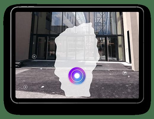 Tablette, avec dans l'écran une photo de l'entrée d'un batiment. Par dessus cette photo, en Réalité Augmentée, il y a une forme blanche, comme l'entrée d'une grotte.