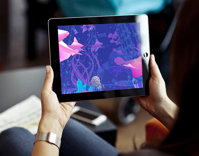 Photographie d'une personne assise tenant une tablette dans ses mains. On ne voit pas le visage de la personne, on voit l'écran de la tablette. Dans l'écran, on voit le monde d'Abyss, un monde sous-marin fantastique, fond bleu, poissons roses et diverses plantes aquatiques