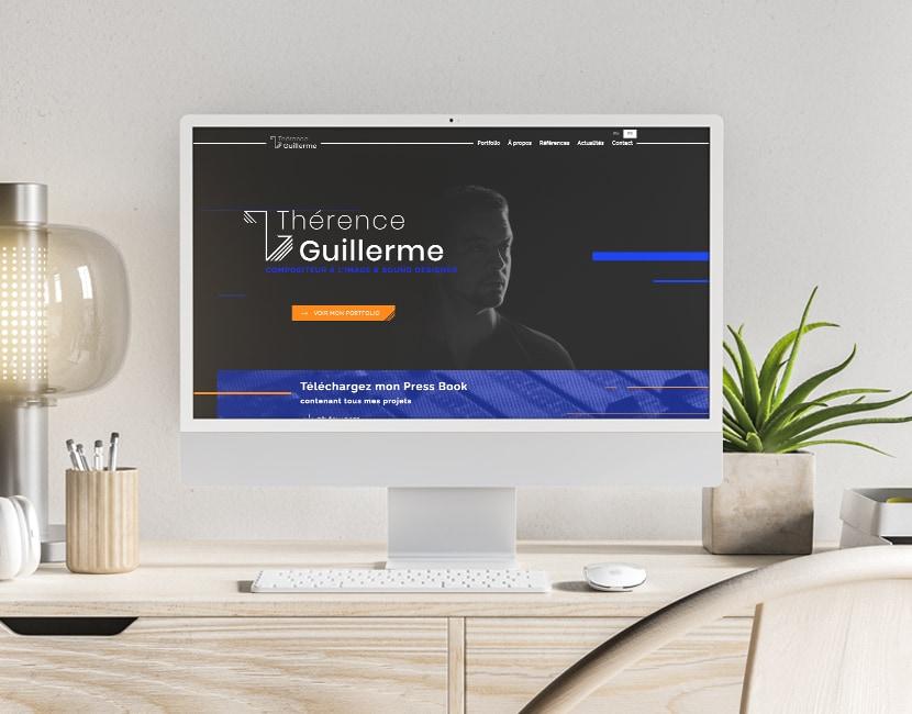 Photographie d'un ordinateur sur un bureau. Dans l'écran, on voit la page d'accueil du site de Thérence Guillerme. La page est sur fond noir, on voit le nom de thérence et sa photo.