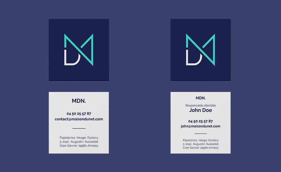 Carte de visite de l'agence MDN. La carte est carrée. Sur le recto, on retrouve le sigle du logo sur fond bleu marine, avec le sigle en vert fluo et blanc. Sur le verso, il y a les informations. Il y a 2 versions du verso. La première est générale, on trouve les infos de l'agence comme le téléphone, le mail et l'adresse. Sur la deuxième version, on retrouve le nom et le métier d'un membre de l'équipe en plus des informations précédentes.
