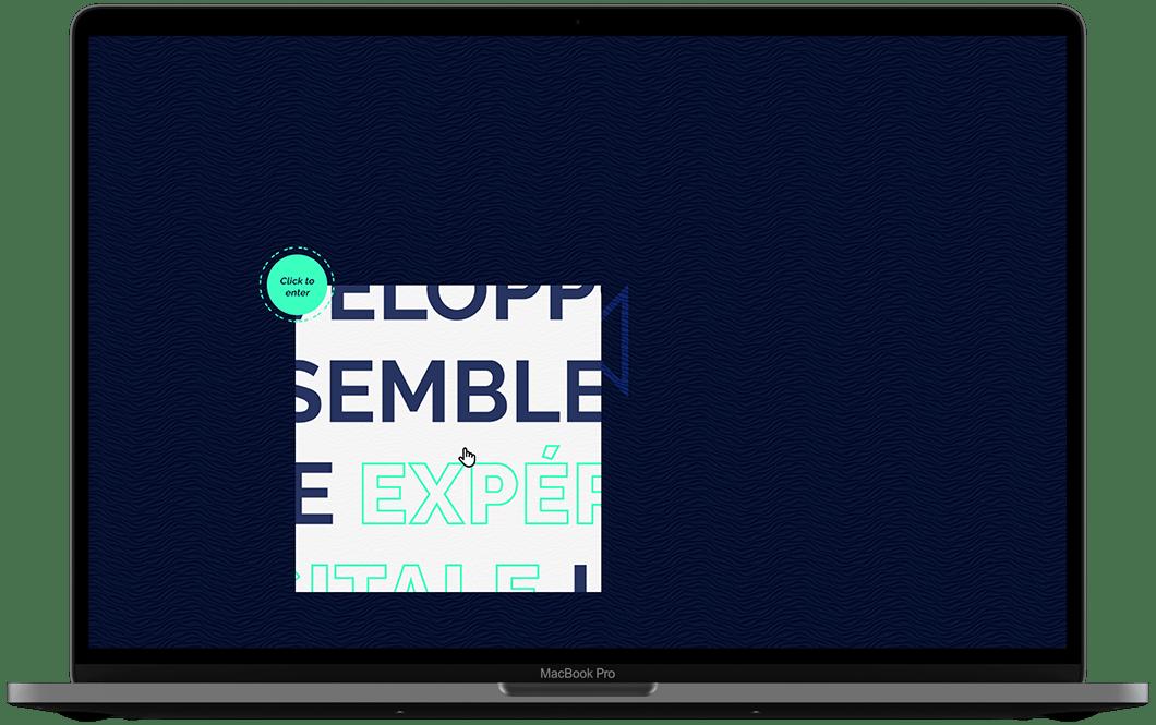 Photographie d'un ordinateur. Dans l'écran, on voit un fond bleu marine texturisé, en bas à droite de l'écran, il y a un carré qui fait comme une fenêtre vers l'intérieur du site, au niveau du curseur. Dans une petite bulle, il est écrit