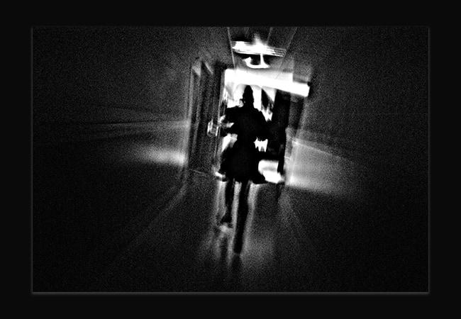 Photo abstraite en noir et blanc. Il y a un grain sur l'image et on aperçoit comme une silhouette difforme.