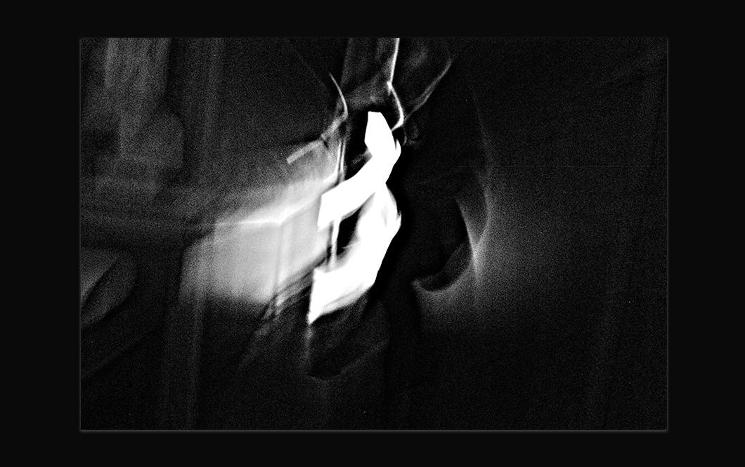 Photo abstraite en noir et blanc. Il y a un grain sur l'image et on aperçoit des formes lumineuses au centre.