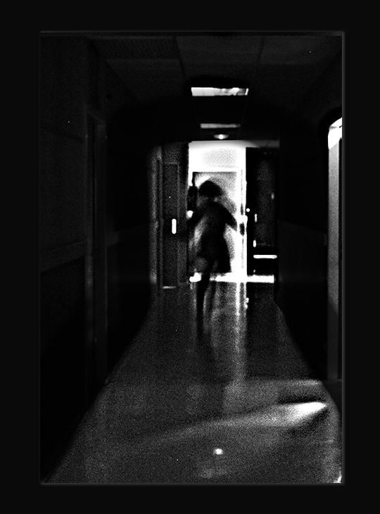 Photo à la limite de l'abstrait, en noir et blanc. Il y a un grain sur l'image et on aperçoit comme une silhouette difforme, qui court dans un couloir.