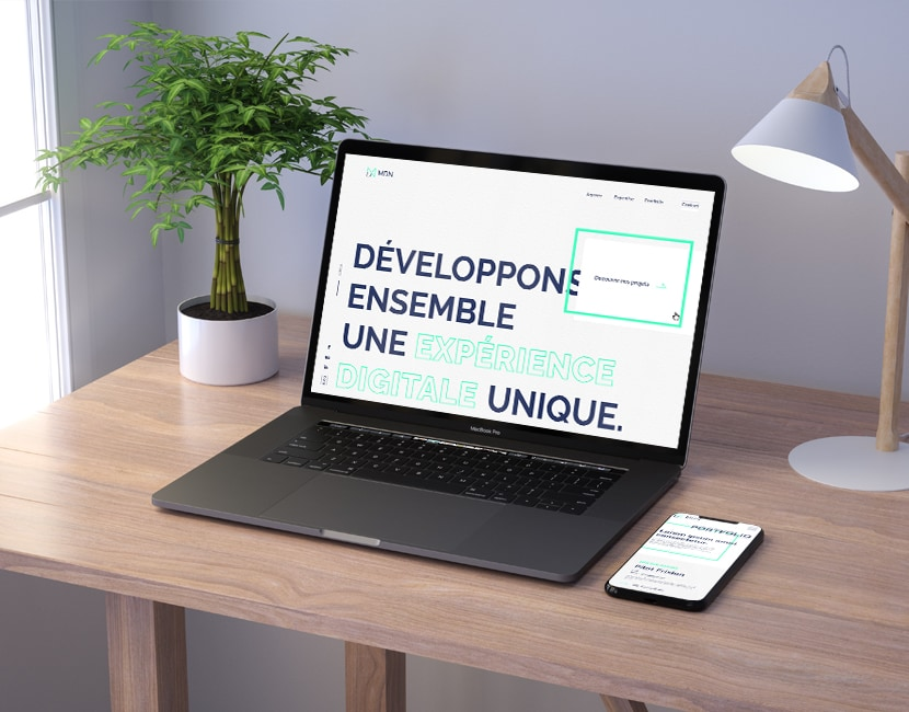 Un ordinateur portable est posé sur un bureau. Dans l'écran on voit la page d'accueil du site MDN, avec écrit