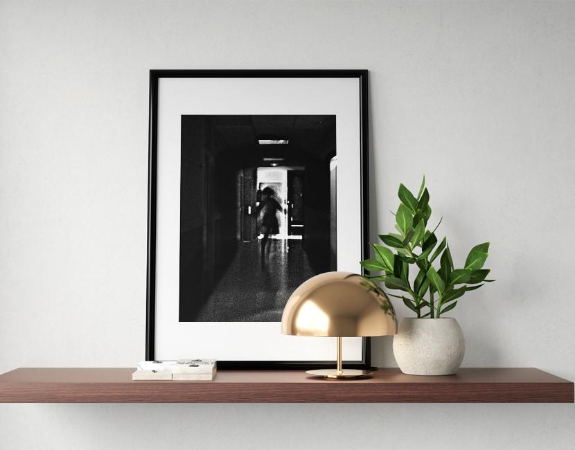 Une photo d'un cadre posé sur une étagère avec une plante verte. Dans le cadre, il y a une photo à la limite de l'abstrait, en noir et blanc. Il y a un grain sur l'image et on aperçoit comme une silhouette difforme, qui court dans un couloir.