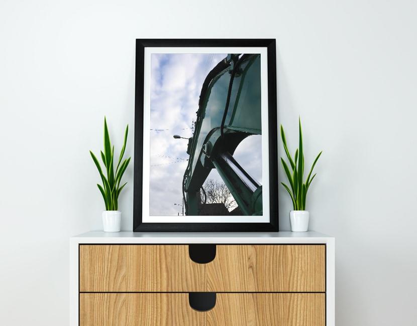 Photo d'un cadre posé sur un meuble en bois, avec 2 plantes vertes. Dans le cadre, on voit la photographie en gros plan et en contre plongée d'une machine de chantier verte. Derrière elle, on voit le ciel avec des nuages.