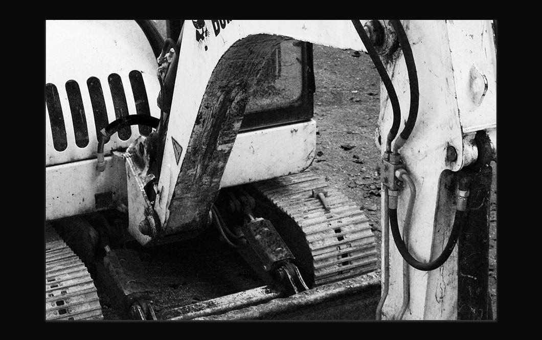 Photographie noire et blanche en plongée d'une partie d'une machine de chantier, on voit les chenilles et le bras de la pelle.