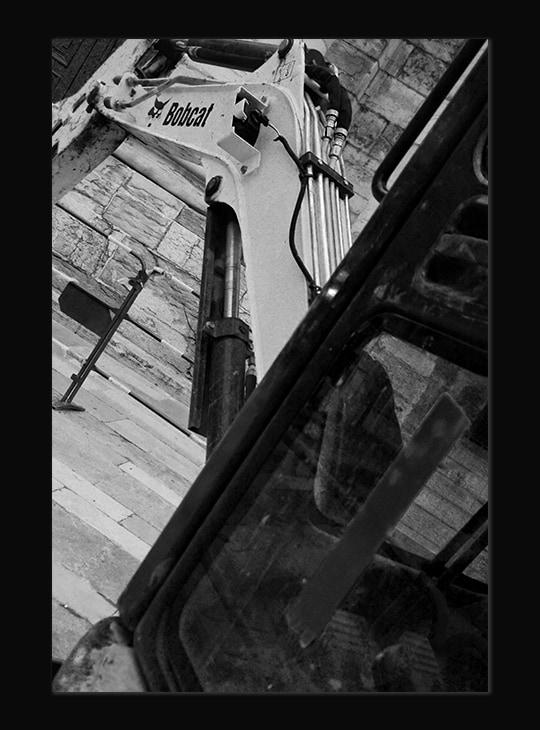 Photographie noire et blanche du bras de la pelle d'une machine de chantier.