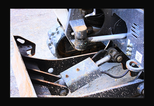 Photographie en plongé d'un gors plan d'une machine de chantier. La machine est beige et grise. Elle est tachée de boue à plusieurs endroits.