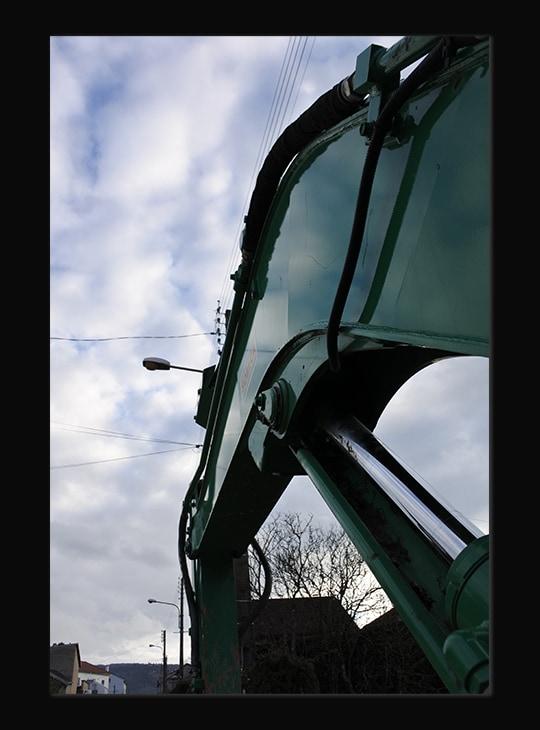Photographie en gros plan et en contre plongée d'une machine de chantier verte. Derrière elle, on voit le ciel avec des nuages.