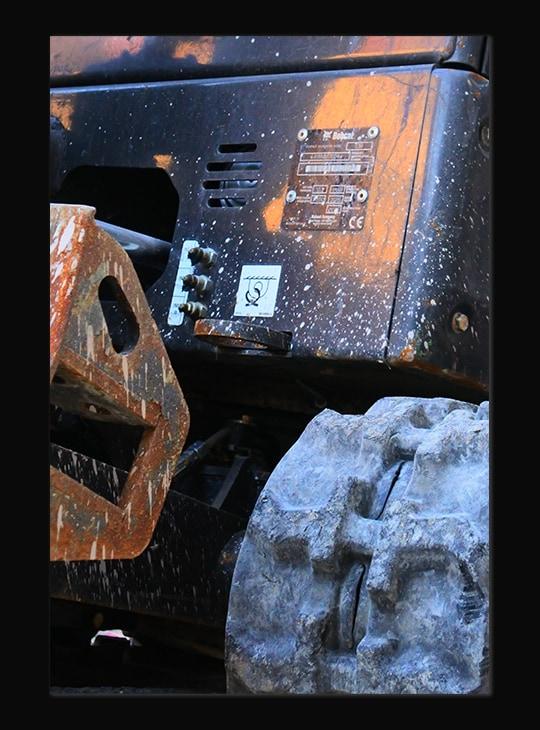 Photographie d'un gros plan d'une machine de chantier noir et beige. On aperçoit un morceau de chenille. La machine est tachée de boue à plusieurs endroits.