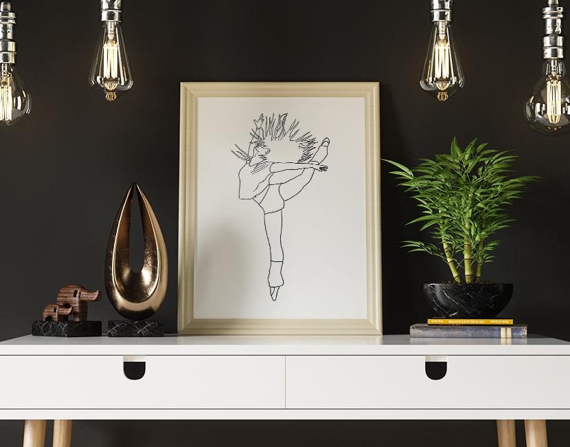 Photographie d'un cadre posé sur un bureau avec des lumières et une plante. Dans le cadre, on voit une illustration au trait, d'une femme en train de danser.