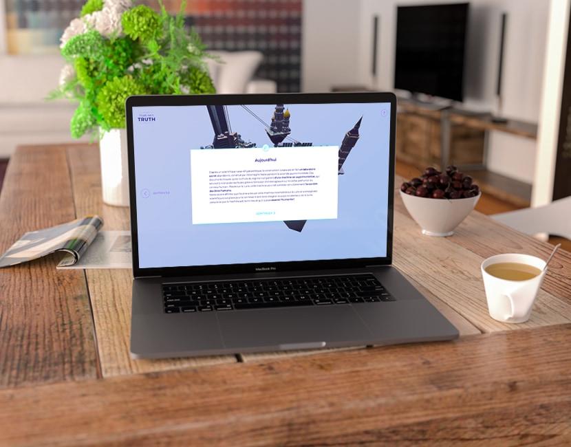 Photographie d'un ordinateur posé sur une table en bois, devant une plante verte. Dans l'écran, on voit le site de Truth isn't truth, avec la vue 3D des ilots en arrière plan, et devant, un bloc blanc avec du texte.