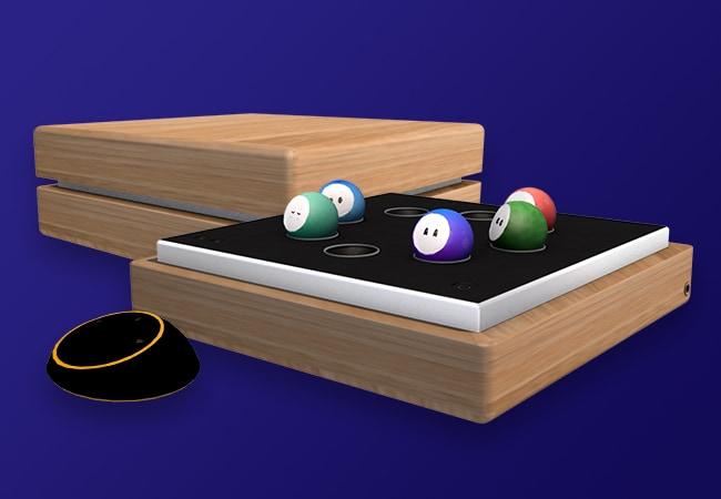 Sur fond bleu foncé, des vues 3D de l'objet Oo'ly. On voit un boitier en bois, carré, séparé en 2 parties dans la hauteur. La partie du haut est un couvercle pour fermer le boîtier, la partie du bas est un plateau noir, avec 8 encoches en cercle pour placer les Oo', un bouton On, et des boutons de volume sonore. A côté du boitier, on voit une sorte de télécommande noir, ronde et plate. Il s'agit du Pod. On aperçoit des boutons sur la surface du dessus.