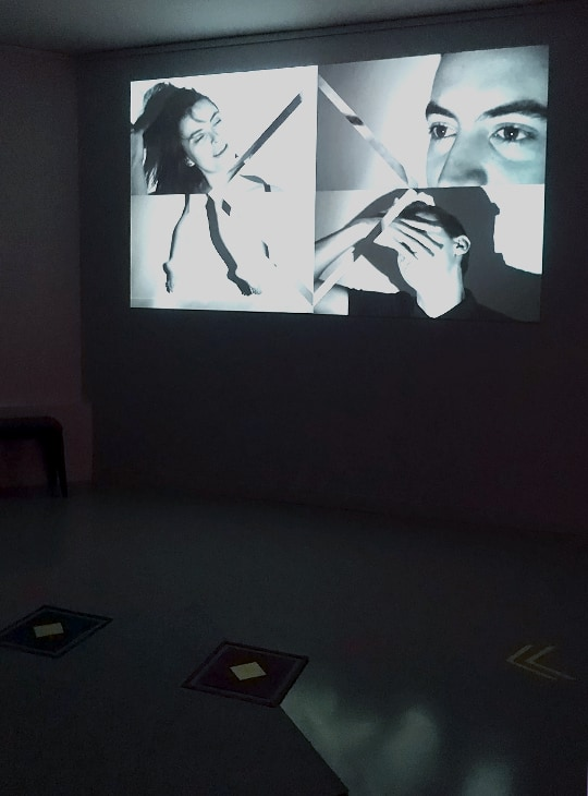Photo de l'expérience une fois mise en place. La photo a été prise dans le noir. On aperçoit au sol le tapis gris, rose et bleu, et au mur, la projection des vidéos controlées par le tapis. Les vidéos sont noires et blanches, car fixes, il n'y a personne sur le tapis pour les activer.