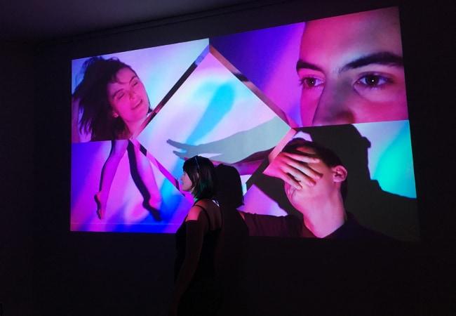Photographie de la projection des vidéos. Elles sont colorées, et donc actives. On voit une personnes devant le mur ou est projeté l'image.